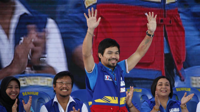 Filipino boxer Manny Pacquiao, who is running for senator, waves to supporters during the start of the national elections campaigning in Mandaluyong city