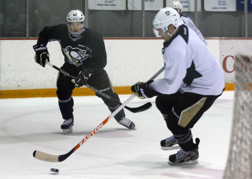 Pittsburgh Penguins' Sidney Crosby, left, is visible through the glass as he skates with Chris Kunitz at an NHL hockey practice on Friday, April 26, 2013, in Canonsburg, Pa. (AP Photo/Keith Srakocic)