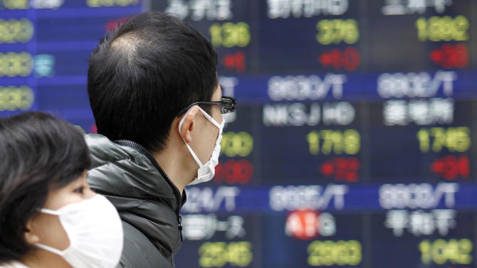 People walk by a stock price display of a securities firm in Tokyo Monday, Dec. 17, 2012. Japan's Nikkei 225 index jumped 1.6 percent to 9,891.15, its highest level since April, after the country's Liberal Democratic Party swept back into power at weekend elections. (AP Photo/Koji Sasahara)