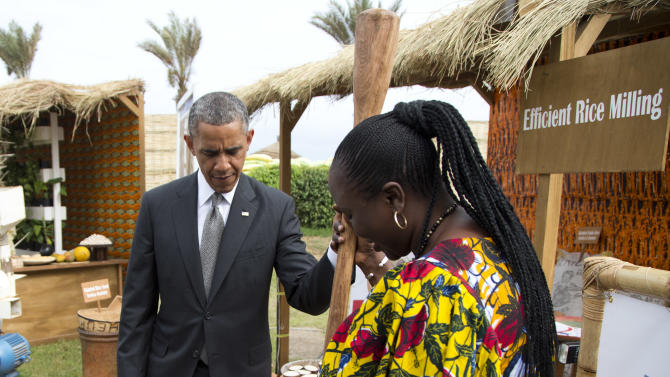 Oumou Gadio, a local farmer, shows U.S. President Barack Obama an old technique for rice milling during a food security expo tour on Friday, June 28, 2013, in Dakar, Senegal. Obama met with farmers, innovators, and entrepreneurs whose new methods and technologies are improving the lives of smallholder farmers throughout West Africa. (AP Photo/Evan Vucci)