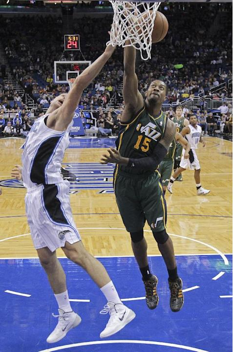 Utah Jazz's Derrick Favors (15) grabs a rebound away from Orlando Magic's Nikola Vucevic, left, of Montenegro, during the second half of an NBA basketball game in Orlando, Fla., Wednesday, Dec