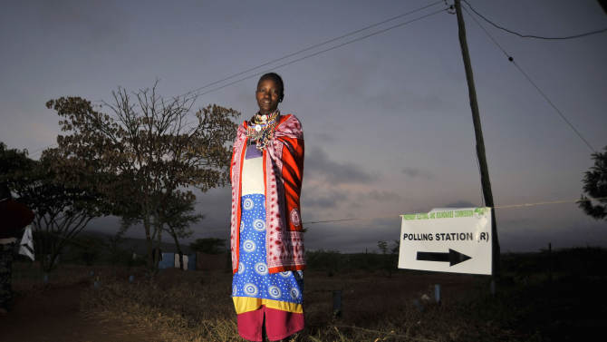 A Masaai woman arrives at a polling station for a general election at dawn in Kumpa, Kenya, Monday, March 4, 2013. Five years after more than 1,000 people were killed in election-related violence, Kenyans went to the polls on Monday to begin casting votes in a nationwide election seen as the country's most important - and complicated - in its 50-year history. (AP Photo/Riccardo Gangale)