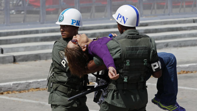 Military police carry a woman who fainted while waiting in line to see the body of Venezuela's late President Hugo Chavez lying in state at the military academy in Caracas, Thursday, March 7, 2013. While Venezuela remains deeply divided over the country's future, the multitudes weeping and crossing themselves as they reached the president's coffin early Thursday were united in grief and admiration for a man many considered a father figure. (AP Photo/Rodrigo Abd)