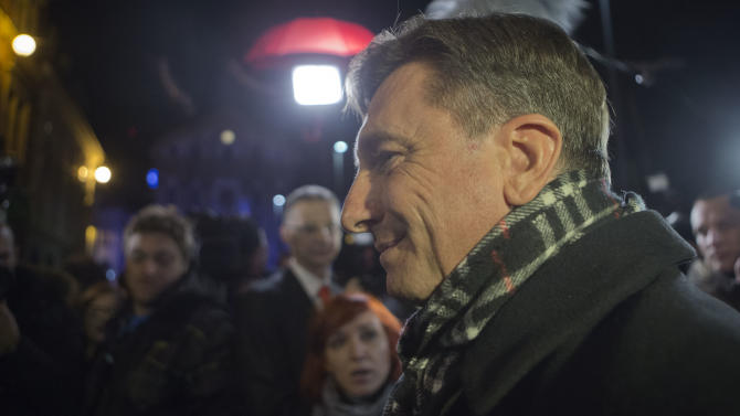 Slovenia's former prime minister Borut Pahor talks to the media outside his headquarters in Ljubljana, Slovenia, Sunday, Dec. 2, 2012.  An exit poll published by Slovenia's state television has shown that Pahor has won the presidential election in the crisis-hit EU country with 67.3 percent of the vote. (AP Photo/Darko Bandic)