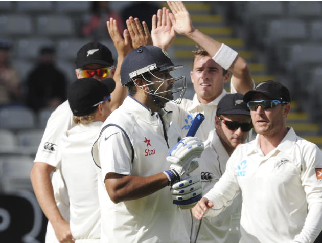 India's Murali Vijay, center, walks, out for 13 as New Zealand celebrate on the third day of the first cricket test at Eden Park in Auckland, New Zealand, Saturday, Feb. 8, 2014. (AP Photo/SNPA, Ross