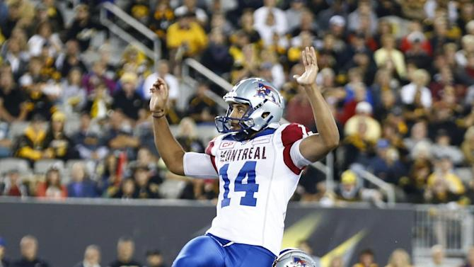 Alouettes' Bede kicks the game winning field goal over Tiger-Cats' Stewart during their CFL football game in Hamilton