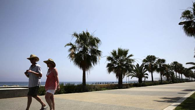 Tourists walk along the promenade in the southern Cypriot city of Limassol on May 17, 2013