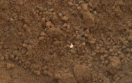 "This image shows part of the small pit or bite created when NASA's Mars rover Curiosity collected its second scoop of Martian soil at a sandy patch called ""Rocknest."" This image was taken by the Mars Hand Lens Imager (MAHLI) camera on Curiosity"