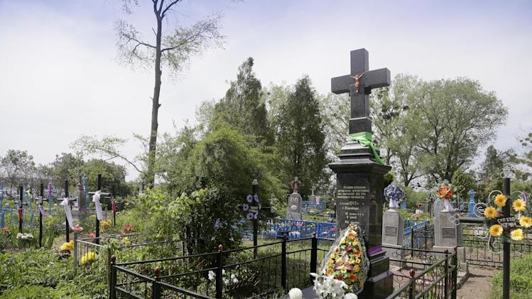 "In this picture taken May 10, 2013, a monument pays tribute to civilians who were burned alive during WWII in Pidhaitsi close to Ukraine's western city of Lutsk. The monument reads: ""To our parents, wives, children, who were murdered by the German occupants on December 3, 1943 in Pidhaitsi. 21 people, including 9 children."" Evidence uncovered by AP indicates that Ukrainian Self Defense Legion commander Michael Karkoc's unit was in the area at the time of the massacre. (AP Photo/Efrem Lukatsky)"