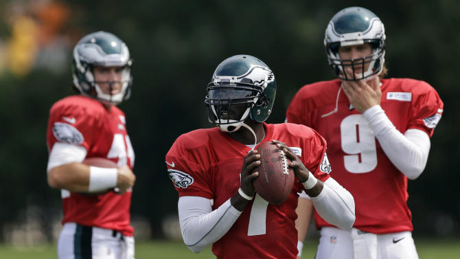 FILE - In this Sept. 5, 2012 file photo, Philadelphia Eagles quarterback Michael Vick, center, drops back to pass as quarterbacks Trent Edwards, left, and Nick Foles look on during NFL football practices at the team's facility in Philadelphia. Vick, who was slated to earn $16 million next season, has agreed to a restructured deal with the Eagles. Vick, who was injured and inconsistent last season, eventually giving way to rookie Nick Foles, now has a three-year contract, and will compete with Foles to see who runs new coach Chip Kelly's offense this season. (AP Photo/Matt Rourke, File)