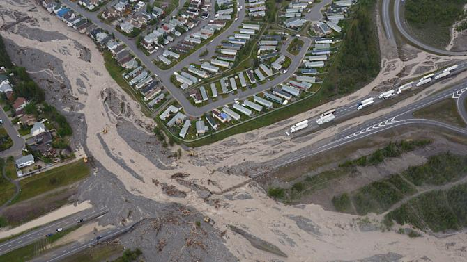 This aerial photo shows the closed Trans-Canada Highway in Canmore, Alberta, on Friday June 21, 2013. Flooding forced the western Canadian city of Calgary to order the evacuation of the entire downtown area on Friday, as the waters reached the 10th row of the city's hockey arena. Communities throughout southern Alberta are dealing with overflowing rivers that have washed out roads and bridges, inundated homes and turned streets into dirt-brown tributaries. About 350,000 people work in downtown Calgary on a typical day. (AP Photo/The Canadian Press, Jonathan Hayward)