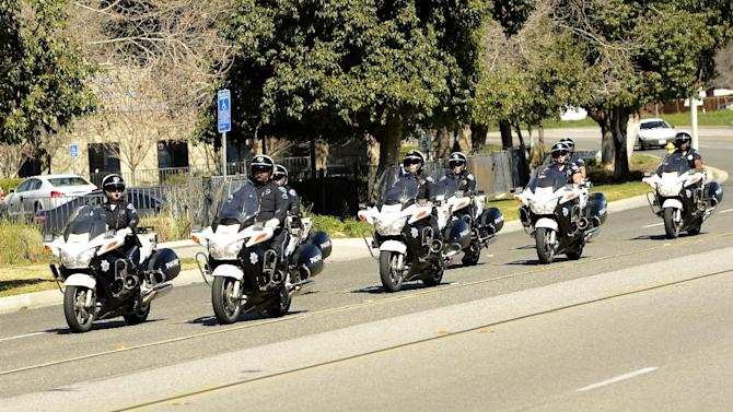 A motorcade escorts the hearse carrying the body of slain San Bernardino County Sheriff's Deputy Jeremiah MacKay in San Bernardino, Calif. on Thursday, Feb. 14, 2013. MacKay was killed in a shootout outside the cabin in Big Bear, Calif. where fugitive ex-cop Christopher Dorner was barricaded inside. The Department held a small service with Honor Guard, and the playing of bag pipes prior to a procession led by a motorcade to Mountain View Mortuary in San Bernardino. (AP Photo/The Sun, Gabriel Luis Acosta)  VENTURA COUNTY STAR OUT; RIVERSIDE PRESS-ENTERPRISE OUT; THE VICTOR VALLEY DAILY PRESS OUT