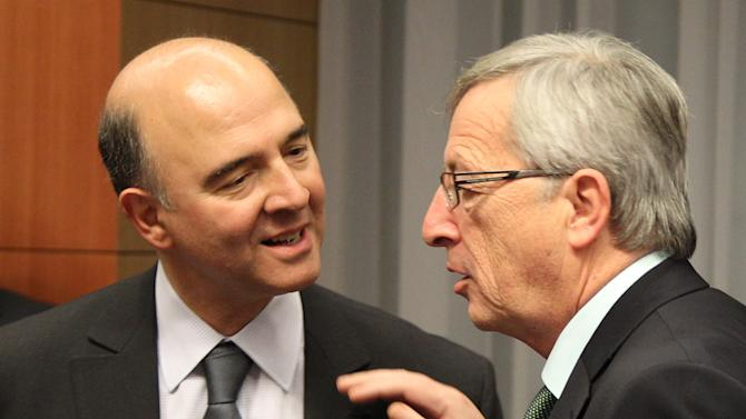 French Finance Minister Pierre Moscovici, left, talks with Luxembourg's Prime Minister and chairman of the Eurogroup Jean-Claude Juncker, during the Eurogroup meeting, at the European Council building in Brussels, Monday, Dec. 3, 2012. Details of a plan for Greece's to reduce its heavy debt by buying some of it back at bargain prices will be presented Monday in Brussels to finance ministers from the 17 European Union countries that use the euro. (AP Photo/Yves Logghe)