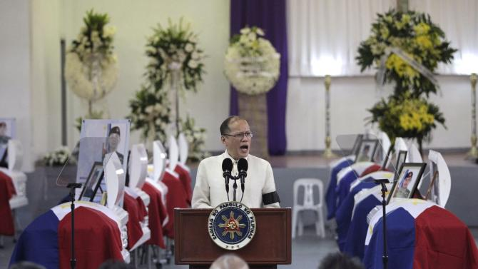 Philippine President Benigno Aquino delivers a speech in front of the caskets of the slain members of the Special Action Force (SAF) who were killed in Sunday's clash with Muslim rebels, during a service inside a police headquarters in Taguig city