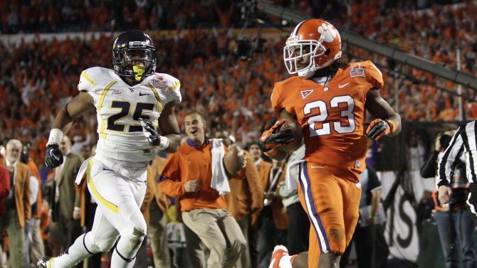 Clemson running back Andre Ellington (23) runs toward the end zone for a 68-yard touchdown as West Virginia  defensive back Darwin Cook (25) trails during the first half of the Orange Bowl NCAA college football game Wednesday, Jan. 4, 2012, in Miami. (AP Photo/J Pat Carter)