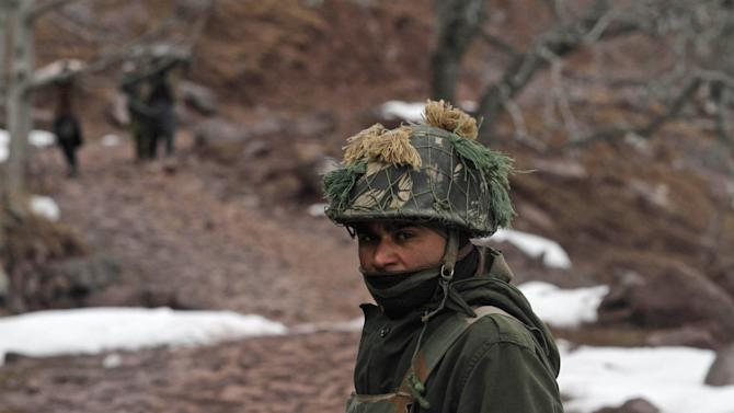 """An Indian army soldier patrols near the Line of Control (LOC), the line that divides Kashmir between India and Pakistan, in Churunda village, about 150 Kilometers (94 miles) northwest of Srinagar, India, Tuesday, Jan. 15, 2013. India's relations with archrival Pakistan """"cannot be business as usual"""" in the wake of a spate of attacks in Kashmir, Prime Minister Manmohan Singh said Tuesday in a statement that threatens to ratchet up tensions in the wake of the Himalayan violence. A series of tit-for-tat attacks, including the beheading of an Indian soldier, across the LOC that divides the Himalayan region has killed two Pakistani and two Indian soldiers over the past 10 days. (AP Photo/Mukhtar Khan)"""