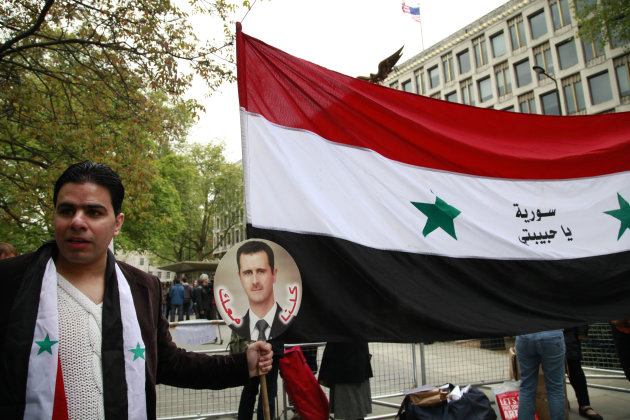 A Syrian supporting the regime of Syrian President Bashar Assad, holds a placard with his picture and the national flag as he participates in a protest outside the US Embassy in central London, Saturd