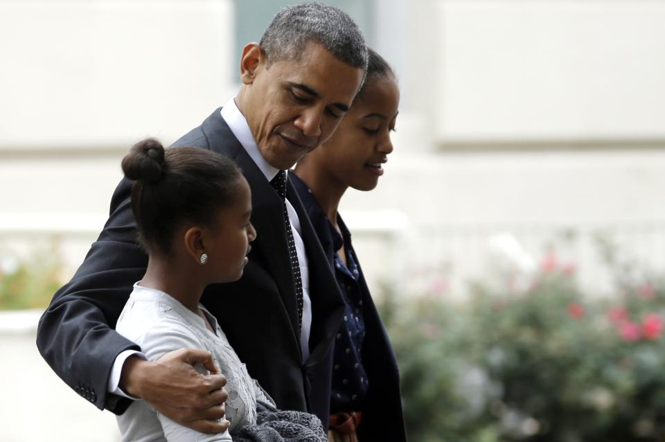 President Barack Obama hugs his daughter Sasha as he walks with Malia as they leave St. John's Episcopal Church to walk across Lafayette Park as they return to the White House in Washington, on Sunday, Oct. 28, 2012. (AP Photo/Jacquelyn Martin)