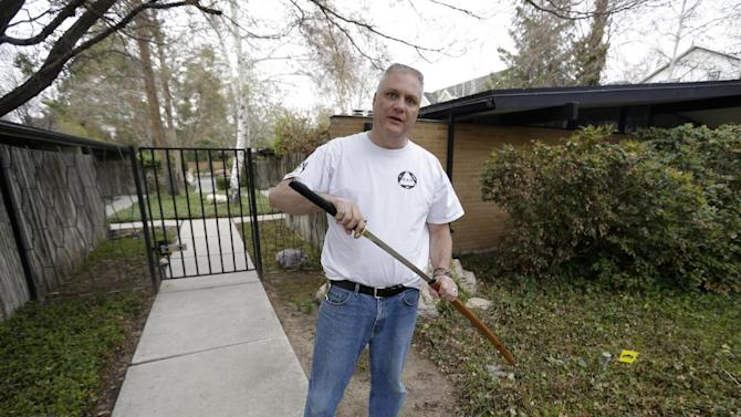 Kent Hendrix, 47, holds his Samurai sword near his house Tuesday, April 23, 2013, in Salt Lake City. Hendrix, a Samurai sword-wielding Mormon bishop came to the aid of a woman who was being attacked in front of his house. Hendrix woke up Tuesday to his teenage son pounding on his bedroom door and telling him somebody was being mugged. Hendrix grabbed a 29-inch Samurai sword and rushed out the door. He says the man attacking a woman jumped back and ran down the street after he drew the sword. The man was chased until he jumped in his car and drove away. (AP Photo/Rick Bowmer)