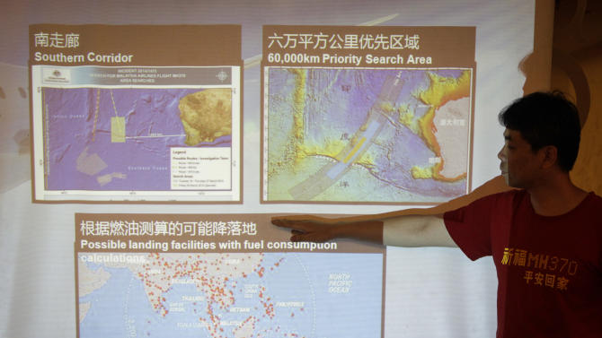 FILE - In this Feb. 20, 2015 file photo, Jiang Hui, a Chinese family member of a passenger onboard the missing Malaysia Airlines Flight 370, points at a map during a press conference at a hotel in Kuala Lumpur, Malaysia. Australia, Indonesia and Malaysia will lead a trial to enhance the tracking of the aircraft over remote oceans, allowing planes to be more easily found should they vanish like Malaysia Airlines Flight 370, Australia's transport minister said Sunday, March 1, 2015. The announcement comes one week ahead of the anniversary of the disappearance of the flight, which vanished in 2104 on a flight from Kuala Lumpur to Beijing with 239 people on board. No trace of the plane has been found. (AP Photo/Joshua Paul, File)
