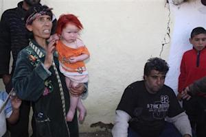 Bulgarian Roma Ruseva holds daughter next to husband Atanas, in front of their house in Nikolaevo