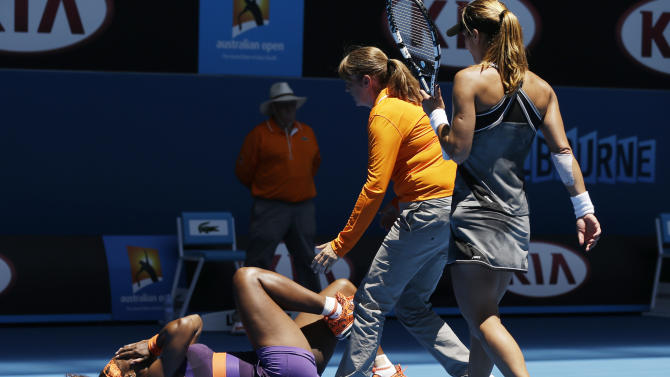 Chair umpire Kerrilyn Cramer, centre, and opponent  Romania's Edina Gallovits-Hall, right, come to the aid of Serena Williams of the US after she fell during her first round match at the Australian Open tennis championship in Melbourne, Australia, Tuesday, Jan. 15, 2013. (AP Photo/Rob Griffith)