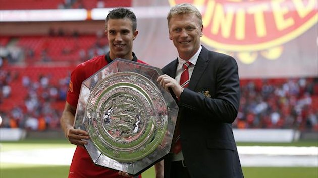 Manchester United's Manager David Moyes holds the trophy with goal scorer Robin van persie after their team won the English Community Shield match against Wigan Athletic at Wembley Stadium in London, August 11, 2013.