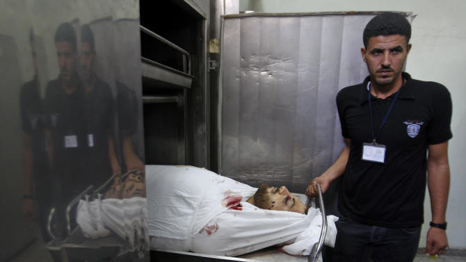 A Palestinian morgue worker shows the body of Hamas militant Ismail al-Tali at the morgue of in Kamal Edwan Hospital, in Beit Lahiya, northern Gaza Strip, Wednesday, Oct. 24, 2012. Dozens of rockets and mortars from the Gaza Strip pummeled southern Israel early Wednesday and an Israeli airstrike killed al-Tali, in a sharp escalation of violence following a landmark visit to Gaza by Qatar's leader.(AP Photo/Hatem Moussa)