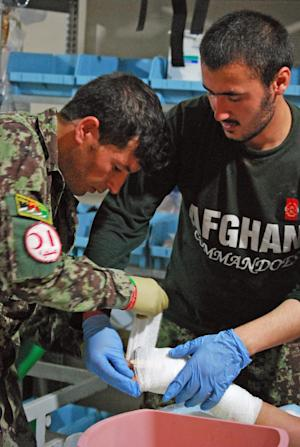 Afghan National Army medics bandage the hand of a wounded Afghan policeman on Tuesday, June 4, 2013, a medical clinic in Nari District, Kunar Province, Afghanistan. As Afghan forces take over fighting this year, the Afghan National Army is struggling with a shortage of doctors. (AP Photo/Kristin M. Hall)