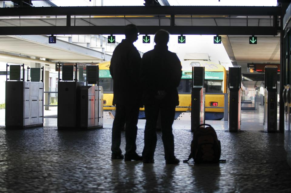 Passengers stand by idle trains at Lisbon's Cais do Sodre train station during a strike by Portuguese trains engineers, Tuesday, Jan. 1, 2013. Portuguese engineers train union called for a partial strikes during January against wage cuts at extra hours, weekends and holidays shifts. (AP Photo/Francisco Seco)