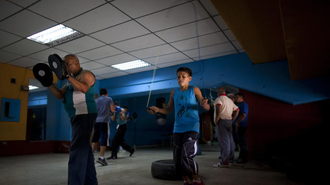 In this May 24, 2012 photo, Miguel Uzcategui, 13, jumps rope as part of his training at a boxing gym in Caracas, Venezuela. Every weekend, boys line up with their gloves to slug it out in a boxing ring that moves around Caracas from parks to plazas to streets in the slums. They're participating in a program supported by the Venezuelan government that aims not only to develop standout fighters but also to expand the sport's reach and give poor teenagers an outlet to stay away from crime, alcohol and drugs. Uzcategui says the sport has given him goals as well as improved self-confidence. (AP Photo/Ariana Cubillos)