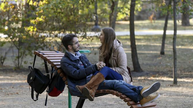 Couple rests on a chair on an autumn day in a park in central Kiev