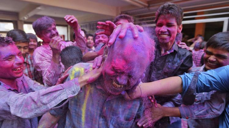 Students apply coloured power onto their teacher's head during Holi celebrations at a school in Ahmedabad