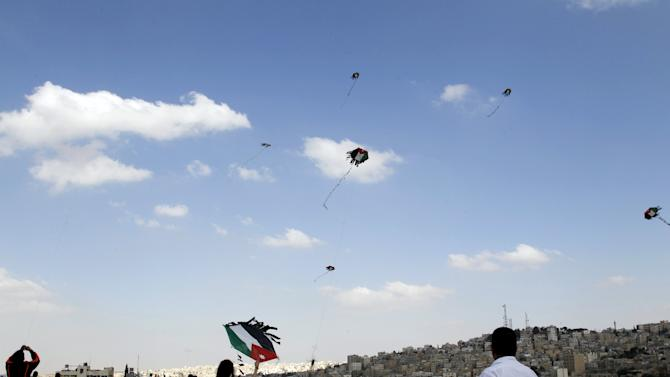 People fly kites with the design of the Jordanian national flag during an event to celebrate Jordan's Independence Day at the Amman Citadel