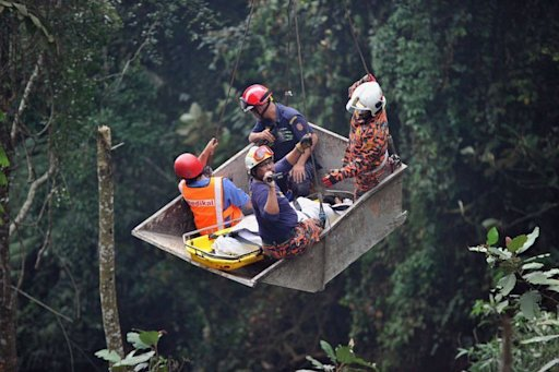 Malaysian rescuers help a passenger (C) after a bus accident near the Genting Highlands, on August 21, 2013