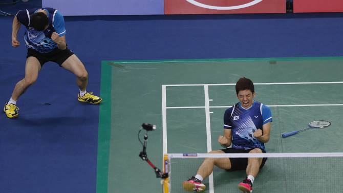 South Korea's Yoo Yeonseong and Lee Yongdae celebrate winning their match against China during the men's team gold medal badminton match at the Gyeyang Gymnasium during the 17th Asian Games in Incheon