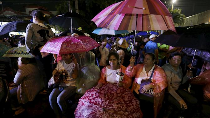 People hold umbrellas in the rain during a procession for the late archbishop of San Salvador Oscar Arnulfo Romero in San Salvador