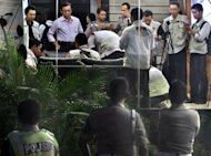 This photograph taken in July 2012 shows Indonesian police observing investigators from the Corruption Eradication Commission (KPK), wearing olive green vests, hauling documents from the headquarters of the traffic police division in Jakarta during a raid related to a corruption case in the procurement of driving simulators
