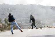 A demonstrator throws a stone at a member of the Palestinian security forces outside the Jalazoun refugee camp near the West Bank city of Ramallah January 12, 2014. REUTERS/Mohamad Torokman