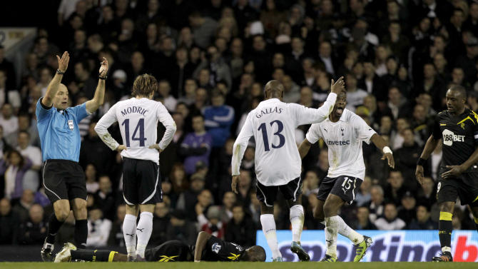 Bolton Wanderers' Fabrice Muamba lies on the pitch after collapsing before being stretchered off as Tottenham Hotspur's Louis Saha, second right, and referee Howard Webb, left, react for medical staff to come onto the pitch during the English FA Cup quarterfinal soccer match between Tottenham Hotspur and Bolton Wanderers at White Hart Lane stadium in London, Saturday, March 17, 2012.  Medics rushed onto the pitch with a defibrillator and treated the 23-year-old Muamba, pumping his chest for around six minutes of treatment. (AP Photo/Matt Dunham)