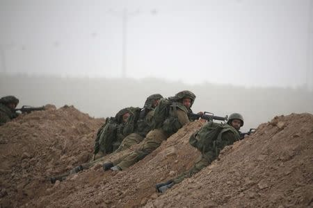 Israeli soldiers take positions outside the northern Gaza Strip, during a gun battle