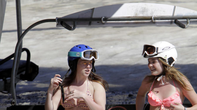 Sydney Warren, left, and Allie Ward, both 15 and from Prince Edward Island, Canada, enjoy the warm sun as they ride the chair lift  while skiing in unusual weather for this time of year at Sunday River in Newry, Maine, on Wednesday, March 21, 2012. (AP Photo/Pat Wellenbach)