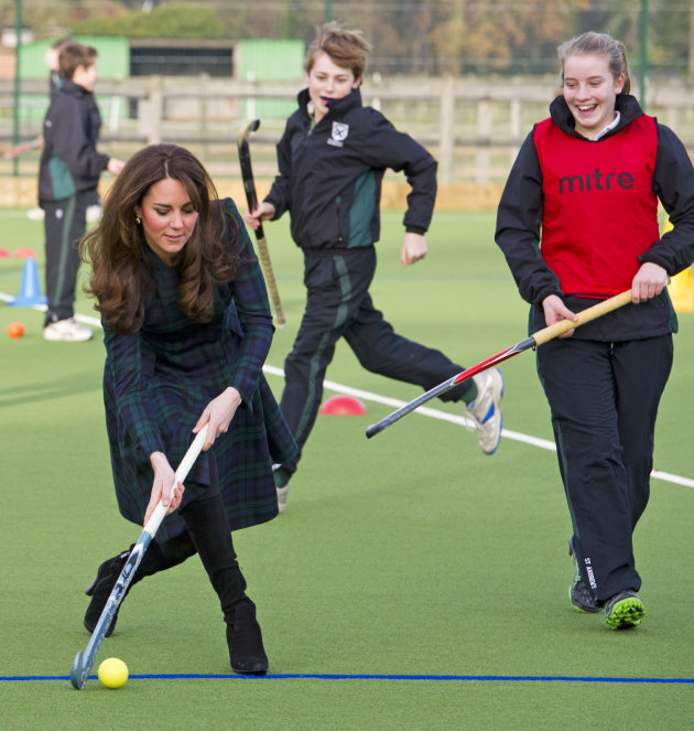 Kate, the Duchess of Cambridge, left,  plays hockey during her visit to St. Andrew's School, where she  attended school from 1986 till 1995, in Pangbourne, England, Friday, Nov. 30, 2012. The Duchess