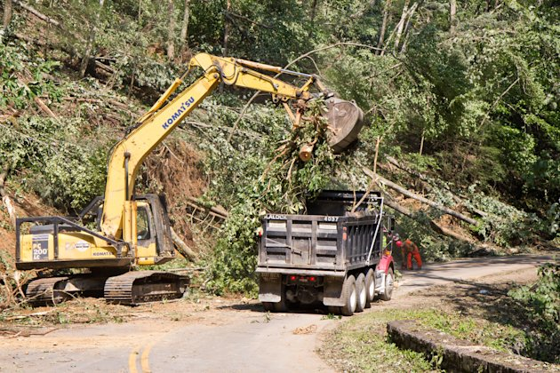 Workers clear storm damage from Great Smoky Mountains National Park on Saturday, July 7, 2012, near Townsend, Tenn., as rangers shifted their focus Saturday from rescue efforts to reopening the popular area to the public. Violent storms on Thursday night led to two deaths and several injuries in the park. (AP Photo/Erik Schelzig)