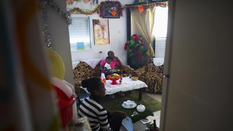 Angesom Solomon, a 28-year-old African migrant from Eritrea, sits with his wife and son at their home in Tel Aviv