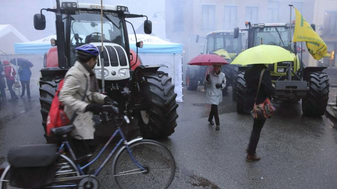 People try to find their way around as European farmers block a crossroad during a demonstration against the TTIP near the European Commission headquarters in Brussels