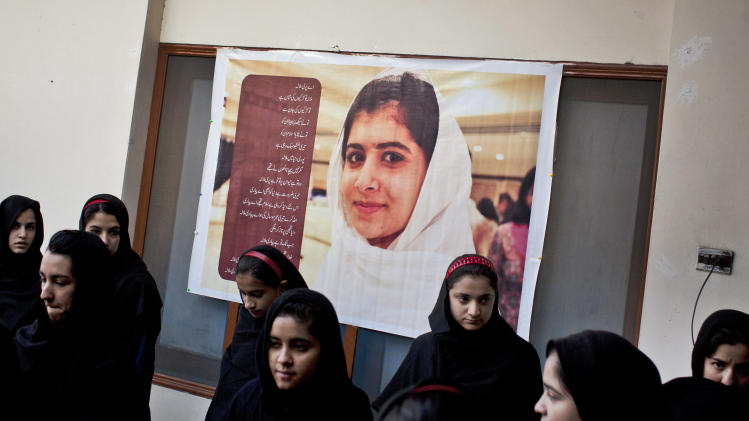 In this Nov. 15, 2012 photo, Pakistani school children gather under a poster of injured classmate Malala at the Khushal School for Girls, as they wait to be collected before classes in Mingora, Swat Valley Pakistan. The poem which runs down one side of the poster talks about Malala's bravery, smile and courage. Malala was shot for her outspoken insistence on girls' education_ and her two friends, Shazia Ramazan and Kainat Riaz were injured by a Taliban gunmen Oct. 8. Shazia and Kainat are to return to school this week for the first time since the shooting. ( AP Photo/Anja Niedringhaus)