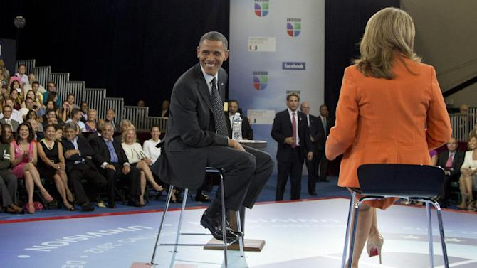 President Barack Obama glances back as he participates in a town hall hosted by Univision and Univision news anchor Maria Elena Salinas, right, at the University of Miami, Thursday, Sept. 20, 2012, in Coral Gables, Fla.  (AP Photo/Carolyn Kaster)