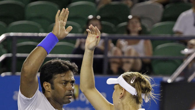 Elena Vesnina of Russia, right,  and Leander Paes of India celebrate a point won against Bethanie Mattek-Sands of the US and Horia Tecau of Romania  during their mixed doubles final at the Australian Open tennis championship, in Melbourne, Australia, Sunday, Jan. 29, 2012. (AP Photo/Sarah Ivey)