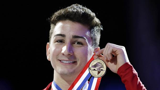Max Aaron holds the gold medal after winning the senior men's championship at the U.S. figure skating championships, Sunday, Jan. 27, 2013, in Omaha, Neb. (AP Photo/Charlie Neibergall)